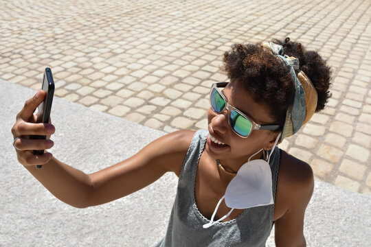 A young smiling african american woman, with teal mirroring sunglasses and a face mask hanging from ear, using her cellphone for selfie and video chats during a journey. Tourism in pandemic times.