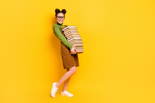 Full length body size profile side view of her she attractive cheerful cheery strong knowledgeable girl carrying book delivery isolated bright vivid shine vibrant yellow color background