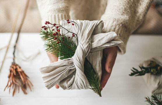 Zero waste Christmas gift. Hands holding stylish gift wrapped in linen fabric with green fir branch and red berries on rustic background. Plastic free sustainable lifestyle