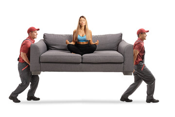 Two movers carrying a sofa with a young woman practicing yoga
