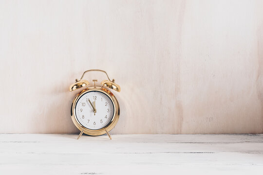 Gold alarm clock on a wooden vintage white table, shabby backdrop. Minimalistic home decor. Modern stylish composition.