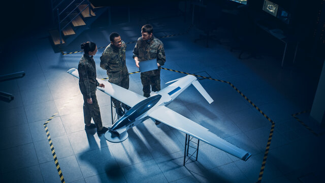 Army Aerospace Engineers Work On Unmanned Aerial Vehicle / Drone. Uniformed Aviation Experts Talk, Using Laptop. Industrial Facility with Aircraft for Performing Surveillance, Warfare Tactics, Attack
