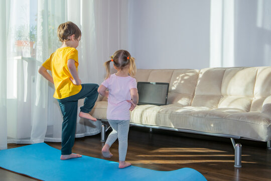 Preschooler boy and girl watching online video on laptop and doing fitness exercises. Kids sports at home, healthy lifestyle, stay at home, online learning, online training.