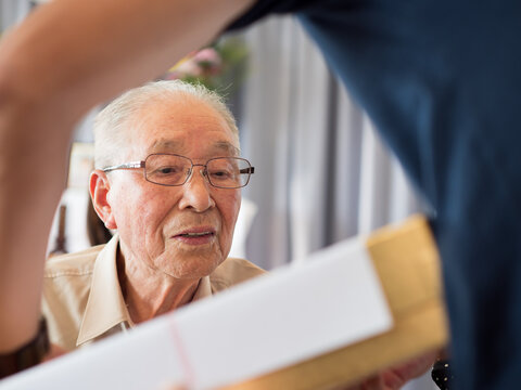 An elderly man looking at something he is receiving with great interest