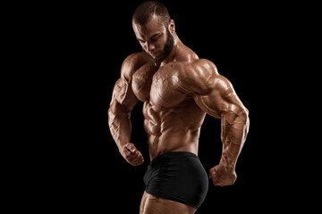 Bodybuilder man isolated on black background. Strong male naked torso abs