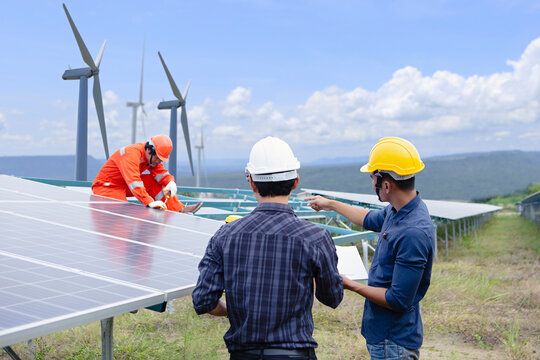 Electrical engineers are installing solar panels and wind turbines. To generate electricity from sunlight and wind. Clean energy concept