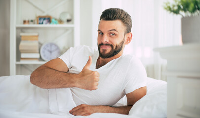 Close up photo of handsome young bearded man lying in bed and relaxing on the morning