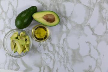 View of two avocados, olive oil bottle and cut avocado in a bowl on white pattern table background