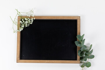 View of a black board surrounded by flowers on white background