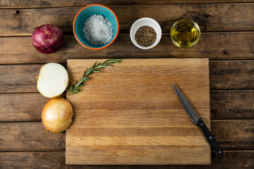 View of a wooden cutting board and knife with onion and seasonings arranged on a on a textured woode