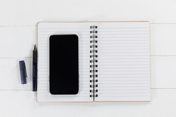 View of a black smartphone, a notebook and a black pen on plain white background