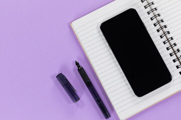 View of a black smartphone, a notebook and a black pen on plain purple background