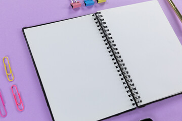 View of a notebook and colorful paperclips on plain purple background