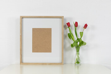 View of a picture frame, with red tulips placed in a glass vase on plain white background