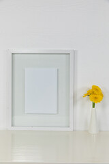 View of a picture frame, with yellow tulips placed in a glass vase on plain white background