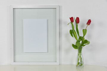 View of an empty picture frame, with red tulips in a glass vase on plain white background