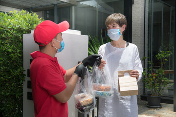 Asian delivery man wearing face mask and gloves in red uniform delivering bag of food and drink to...
