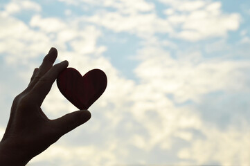 Hand holding a heart against blue sky