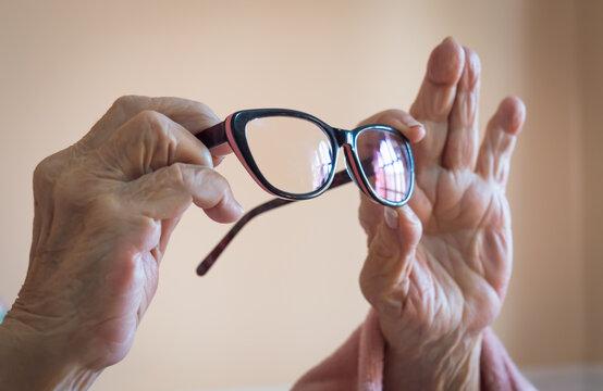 Anteojos lentes sostenidos por las manos de una mujer mayor rosa
