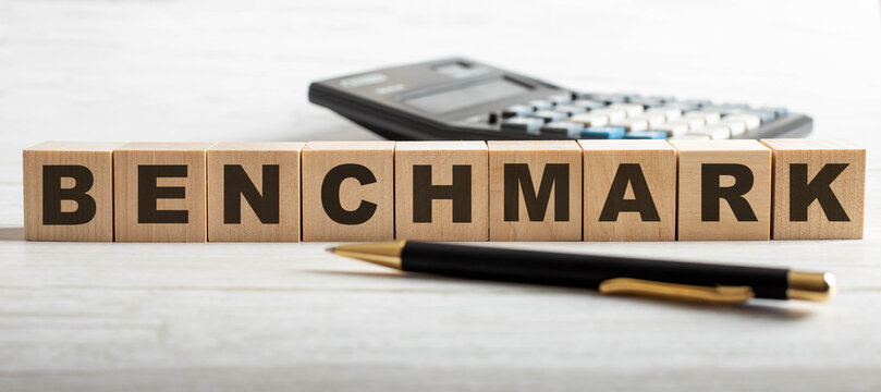 The word BENCHMARK is written on wooden cubes near a calculator and a pen on a light background. Business concept