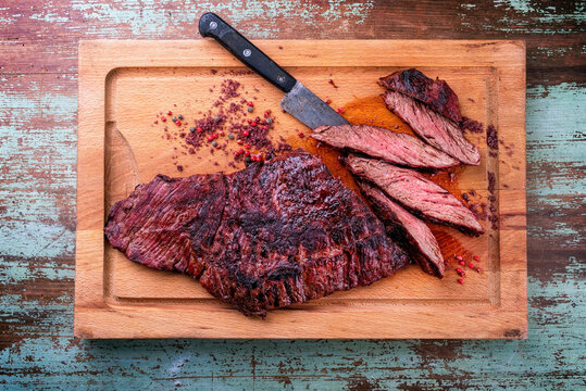 Barbecue wagyu bavette beef steak with red wine salt offered as top view on a rustic wooden board
