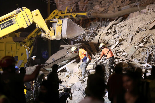 Chilean rescue team members dig through the rubble of buildings which collapsed by the explosion at Beirut's port area