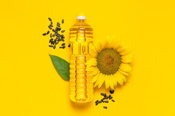 Plastic bottles with sunflower oil, fresh yellow sunflowers, sunflower seeds on yellow background....