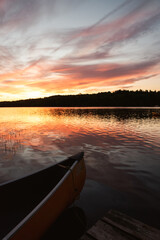 Front of a canoe tied to a wooden dock on a lake at sunrise.