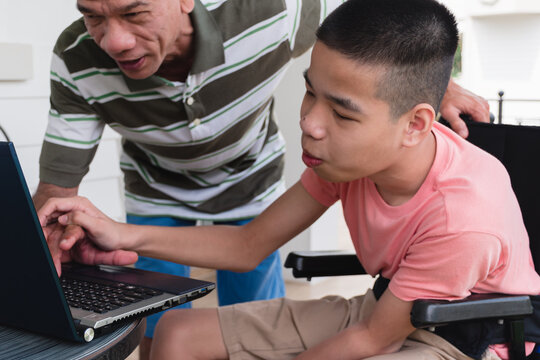 Disabled child on wheelchair use computer notebook with parent in the house,Study and Work at home for safety from covid 19, Life in the education age of special need kid,Happy disability boy concept.