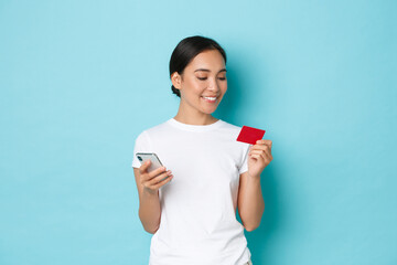 E-commerce, shopping and lifestyle concept. Smiling attractive asian girl order online, looking at credit card while entering digits to mobile phone app, standing light-blue background