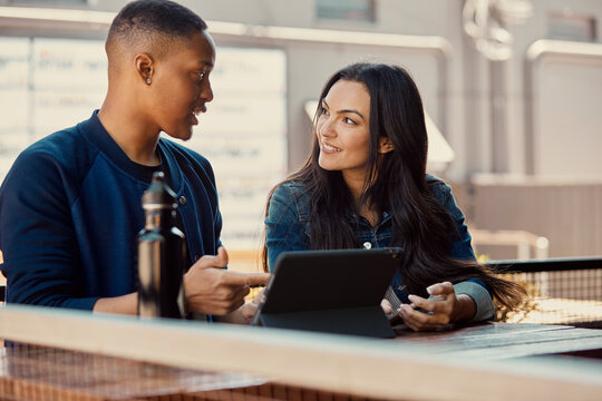 Portrait of young people working on a tablet at an outdoor cafe.