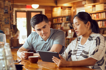 Young man and woman sitting at counter in cafe bookstore looking at tablet