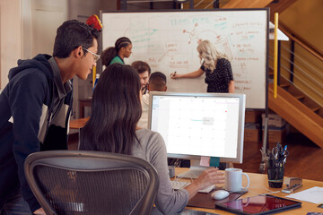 Two co-workers looking at calendar on computer screen, in the background a group of young co-workers discussing brand strategy.