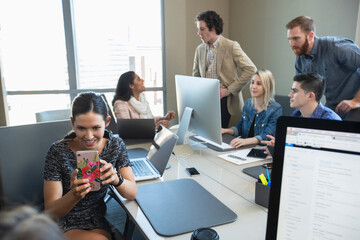 Woman taking picture with mobile phone, while colleagues work in background of conference room
