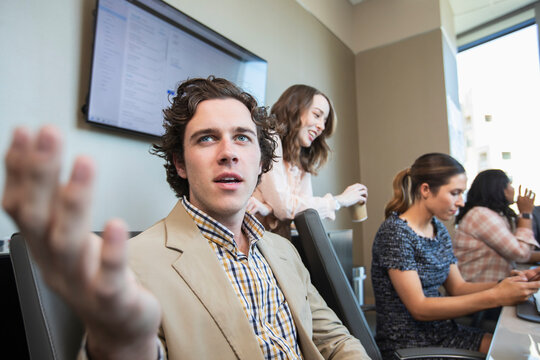 Young man having discussion in conference room with co-workers working in background