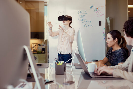 Co-Workers working on computer in office while woman is using Virtual Reality Headset standing in front of dry erase board with flowchart in background