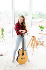 Happy teenage girl with guitar in bright room