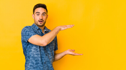 Young caucasian man isolated on yellow bakground shocked and amazed holding a copy space between hands.
