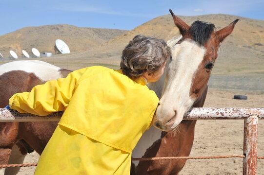 Female rancher bonding with horse.