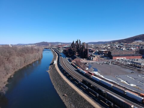 Drone Aerial View Along the Railroad Tracks of Historic Steel Stacks in Bethlehem, Pennsylvania with Mountains in the Distance