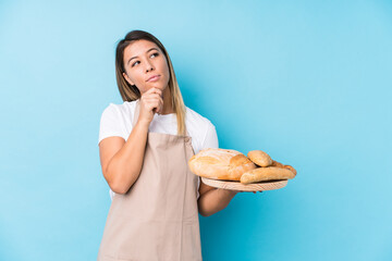 Young caucasian baker woman isolated looking sideways with doubtful and skeptical expression.