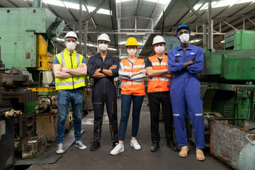 Teamwork of multiethnic engineer with workers standing arms crossed and wearing surgical mask to prevent covid-19 in manufacturing factory