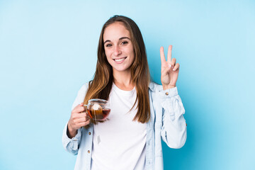 Young caucasian woman holding a tea isolated showing number two with fingers.