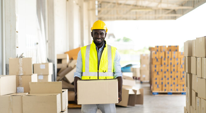 middle aged African American warehouse worker preparing a shipment in large warehouse distribution centre