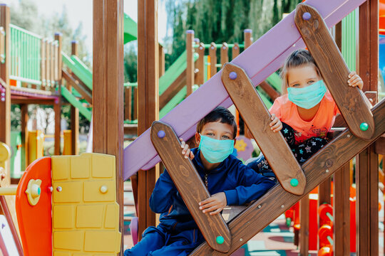 children wearing protective masks playing on playground