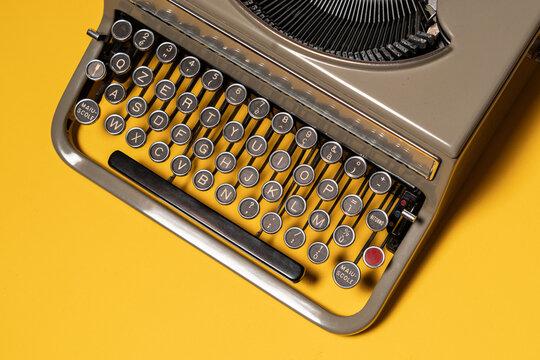 Details of vintage typewriter on yellow background