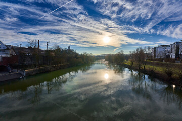 View of the Neckar river in the early morning, green water and blue sky, yellow sun in the background. Plochingen, Germany.