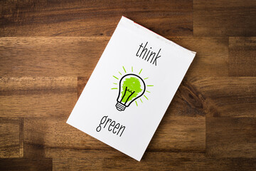 Think green - light bulb and text on a notepad