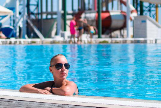 Caucasian blonde rest at pool in aqua park, summer vacation