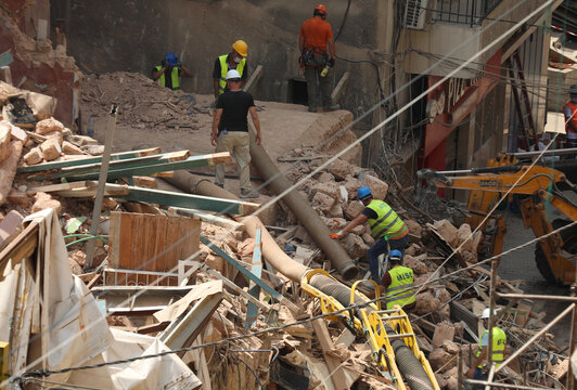 Volunteers and a member of the Chilean rescue team dig through the rubble of buildings which collapsed due to the explosion at the port area, after signs of life were detected, in Gemmayze, Beirut